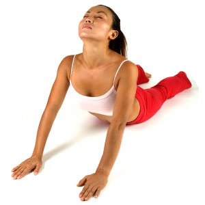 A female fitness instructor demonstrates a yoga position