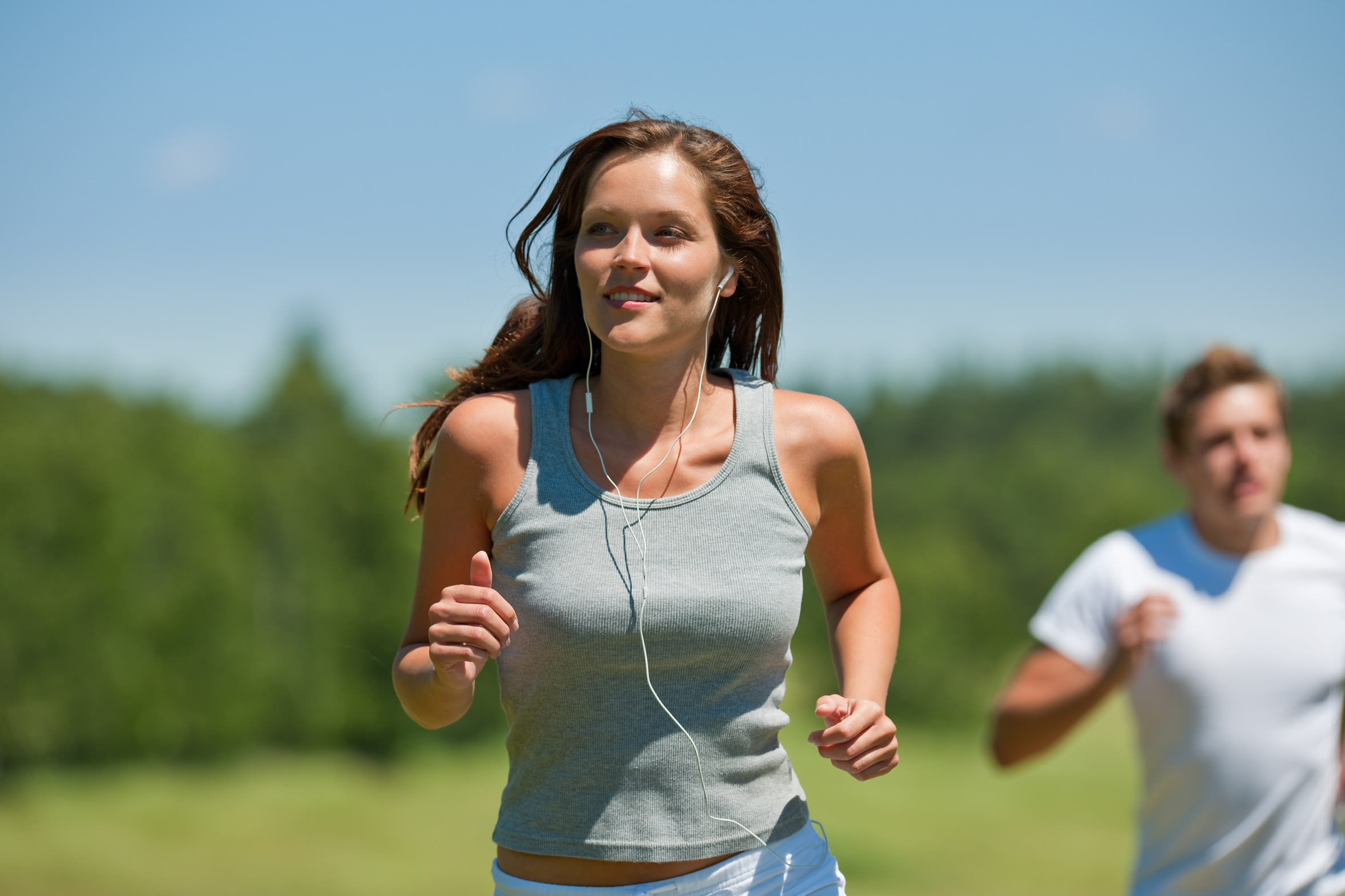 Brown hair woman with headphones jogging