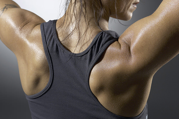 Muscular woman flexing shoulders